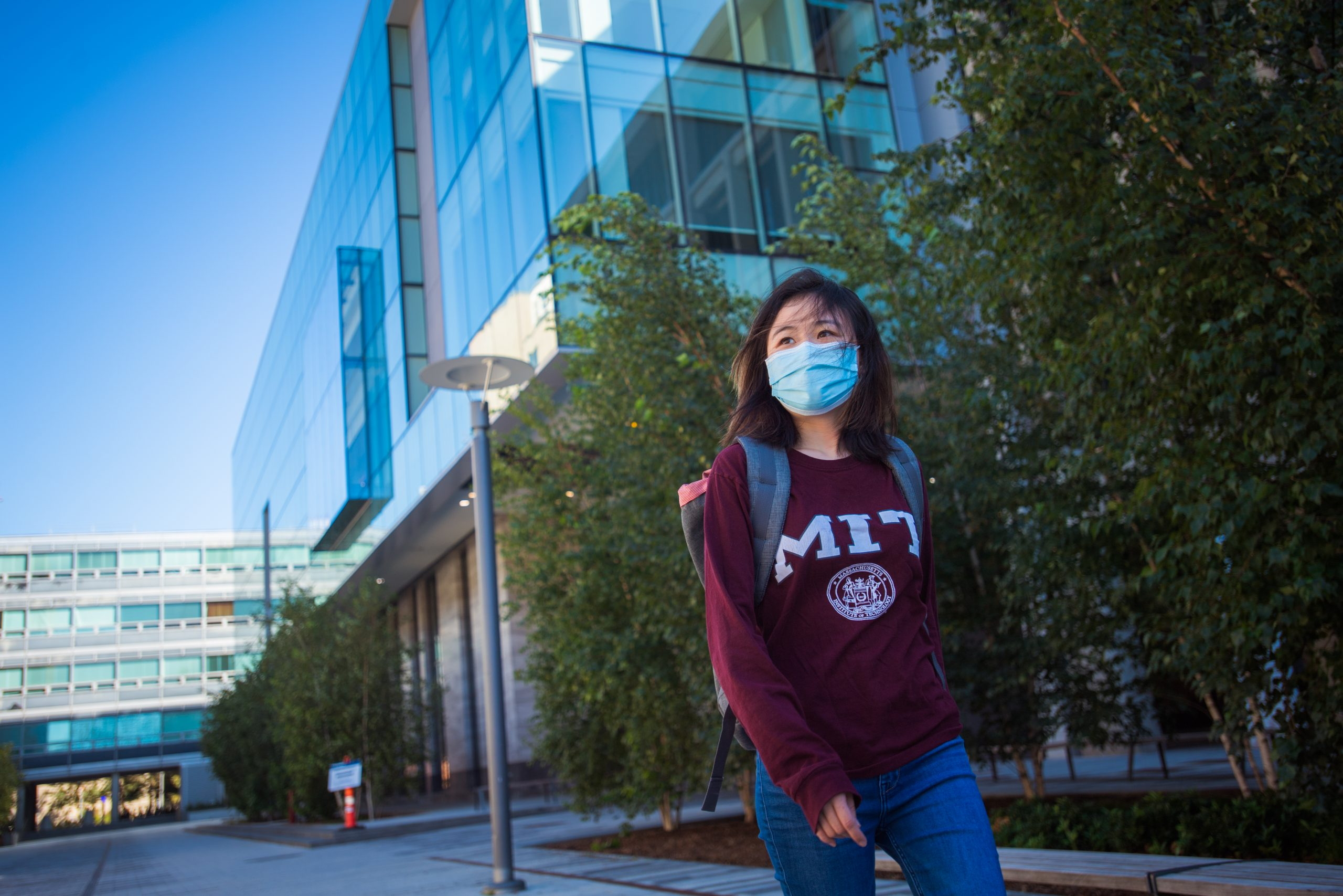 A masked student in an MIT sweatshirt walking on MIT campus